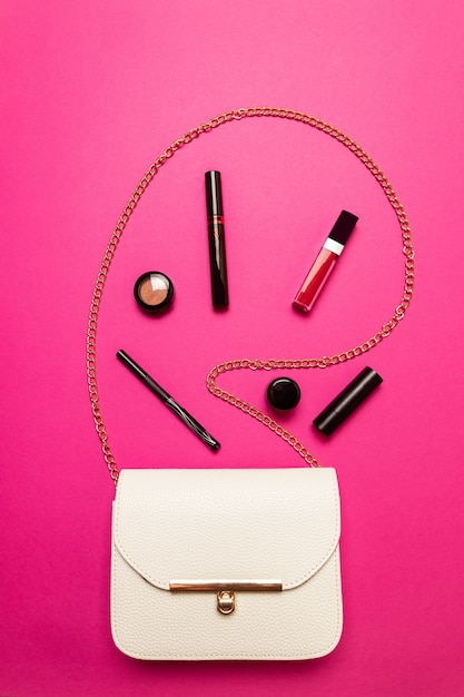 Contents of one white female bag. female bag with copy space on pink background Premium Photo