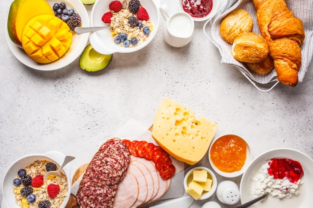 Continental breakfast table with croissants, jam, ham, cheese,  butter, granola and fruit, copy space. Premium Photo