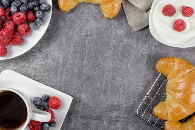 회색 콘크리트 배경에 크로와상 블랙 커피 나무 딸기와 블루 베리와 유럽식 아침 식사 프리미엄 사진