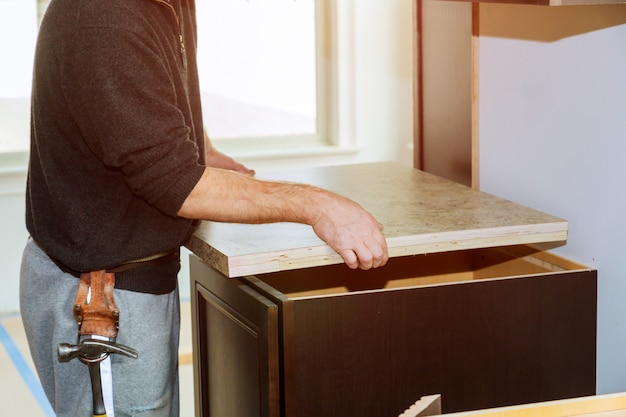 Contractor installing a new laminate kitchen counter top Premium Photo