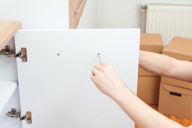 Подрядчик по ремонту собирает новую мебель в современной квартире. Premium Фотографии