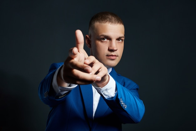 Contrast portrait of a man businessman in an expensive business suit on a dark wall. successful emotional manager businessman posing gestures with his hands on black Premium Photo