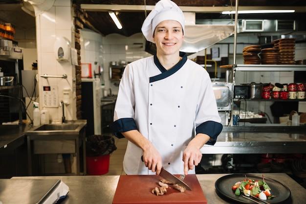皿の上のサラダの近くボード上のカットロースト肉を調理します。 無料写真