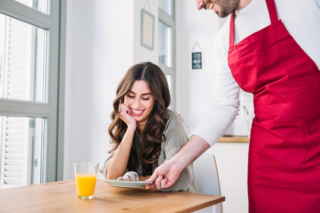 Cook giving croissant to girlfriend Free Photo