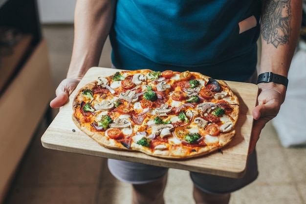Cook tiene un vassoio o un tagliere di legno con pizza con focaccia biologica fatta in casa, ricoperta di verdure, verdure e formaggio Foto Gratuite