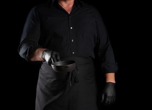 黒のユニフォームで調理し、ラテックスの手袋は空の丸いヴィンテージ黒鋳鉄鍋を保持しています Premium写真