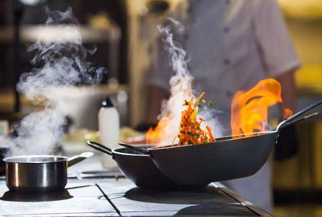 Cook making dinner in the kitchen of high-end restaurant. Premium Photo