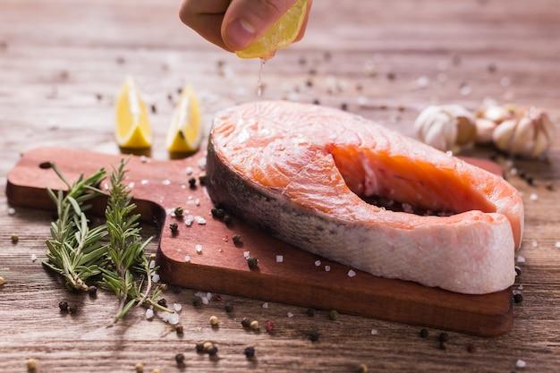 Человек-повар покрывает стейк из лосося и выжимает лимонный сок Premium Фотографии