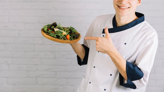 Cook pointing finger at fresh salad on wooden plate Free Photo