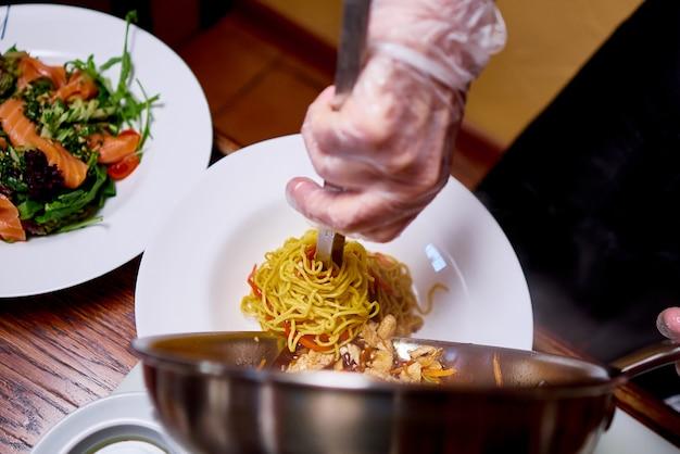 A cook prepares dish on kitchen of the restaurant. Premium Photo