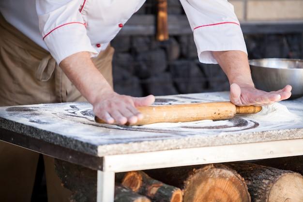 Cook preparing pizza in a restaurant. Premium Photo
