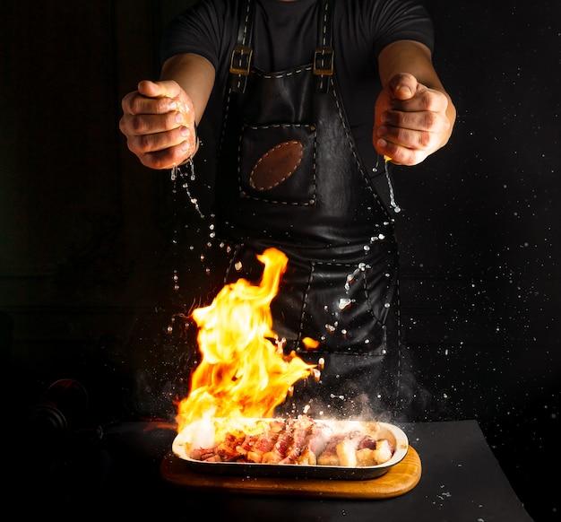 Cook sprinkles lemon juice on flambe meat Premium Photo