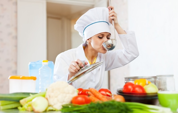 Cook in white uniform tests soup from ladle Free Photo