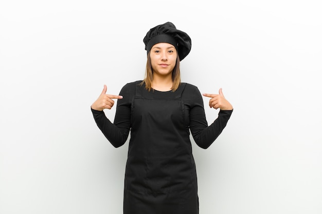 Cook woman looking proud, positive and casual pointing to chest with both hands against white Premium Photo