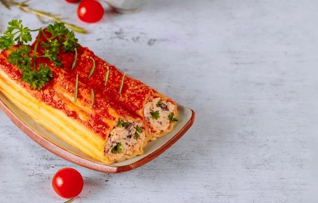 Приготовленные каннеллони на тарелке с томатным декором Premium Фотографии
