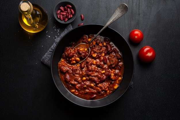 Cooked chili con carne served in bowl ready for eating on dark background. Premium Photo