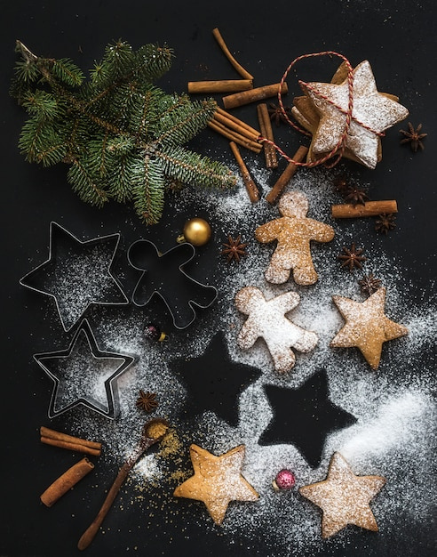 Cooked christmas holiday traditional gingerbread cookies with sugar powder, anise and cinnamon sticks on black Premium Photo