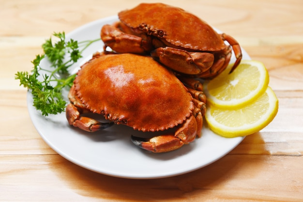 Cooked crab on plate with lemon herbs and spices on the wooden seafood boiled red stone crabs salad Premium Photo