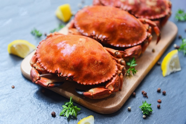 Cooked crabs on wooden board with lemon on plate served on dark plate top view - stone crab steamed seafood Premium Photo
