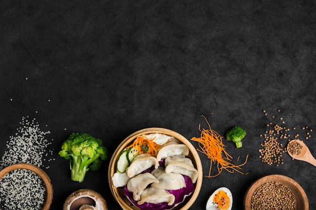 Cooked dumplings inside the bamboo steamer with eggs; broccoli; sesame and coriander seeds on black texture background Free Photo