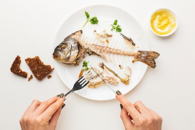 Avanzi di pesce cotto e mani Foto Gratuite