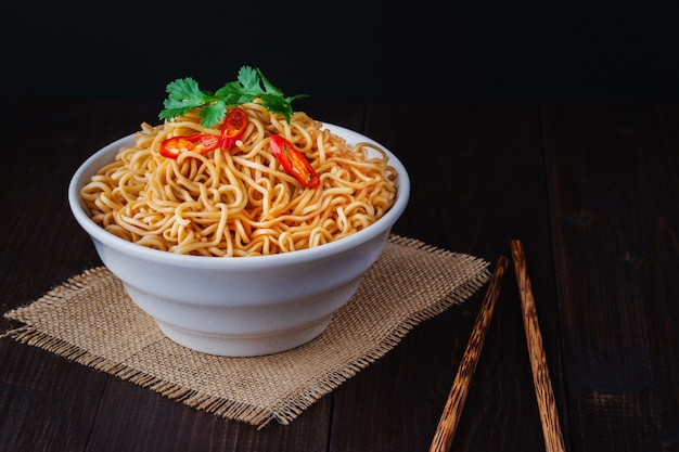 Cooked instant noodles in bowl with chopsticks close up on wooden table Premium Photo