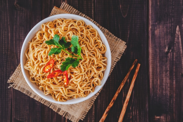 Cooked instant noodles in bowl with chopsticks in top view closeup on wooden table Premium Photo