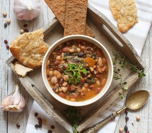 古い木製のテーブルトップビューのボウルで調理された豆類と野菜 Premium写真