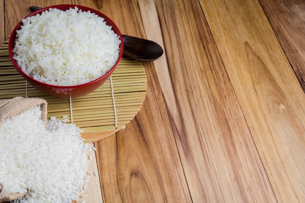 Cooked rice in a red cup placed on the plywood floor. Free Photo
