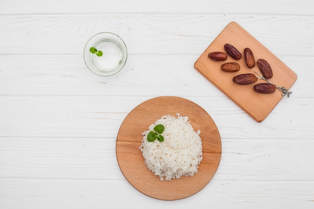 Cooked rice with dates fruit on wooden table Free Photo
