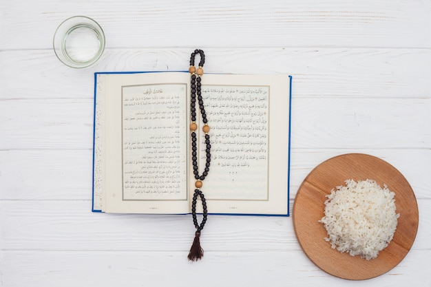 Cooked rice with quran and beads on light table Free Photo