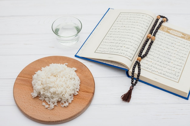 Cooked rice with quran and beads on table Free Photo