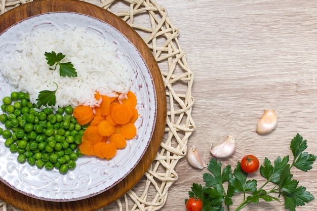 Cooked rice with vegetables and parsley on plate on wooden table Free Photo