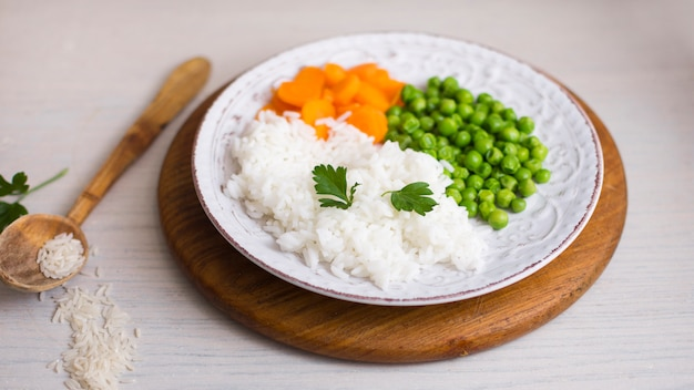 Cooked rice with vegetables on wooden board near spoon Free Photo