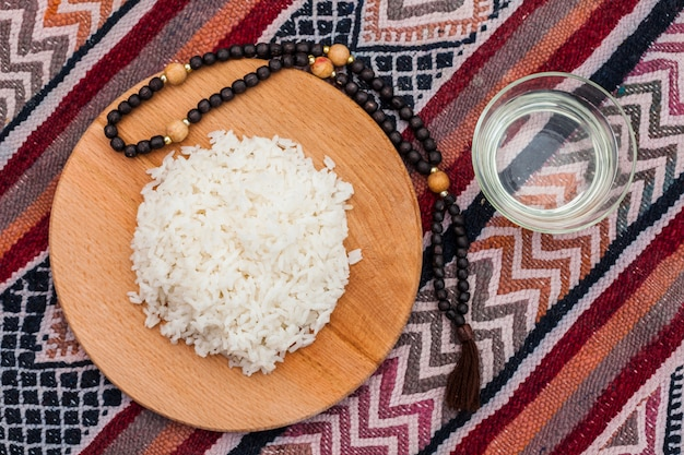 Cooked rice on wooden board with beads Free Photo