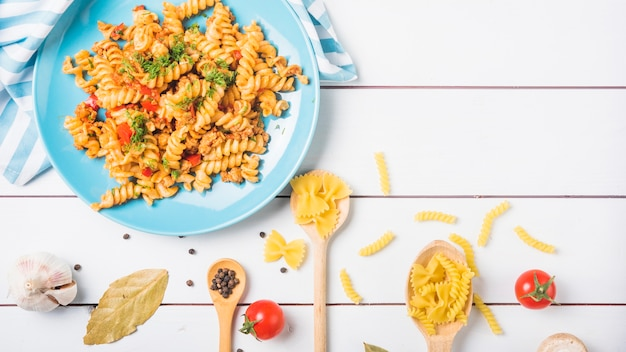 Cooked vegetable pasta fusilli with ingredients on white wooden backdrop Free Photo