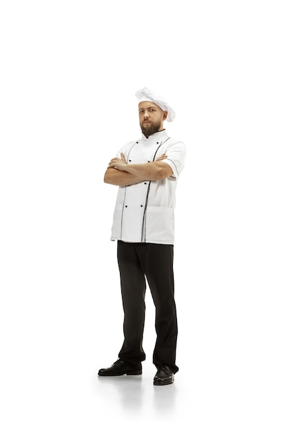 Cooker, chef, baker in uniform isolated on white studio background, gourmet. young man, restaurant cooker's portrait. business, foor, professional occupation, emotions concept. copyspace for ad. Free Photo