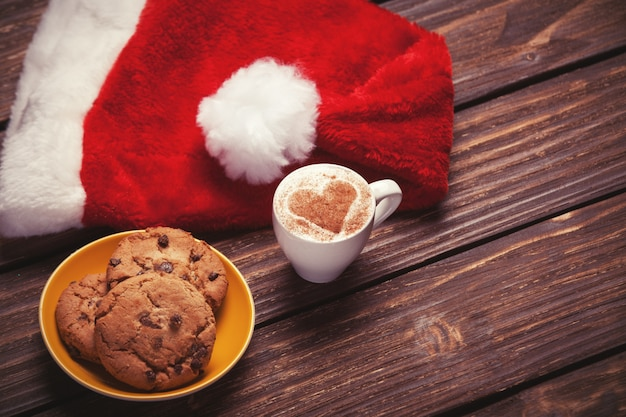 Cookie and cup of coffee with santa's hat on wooden table. Premium Photo