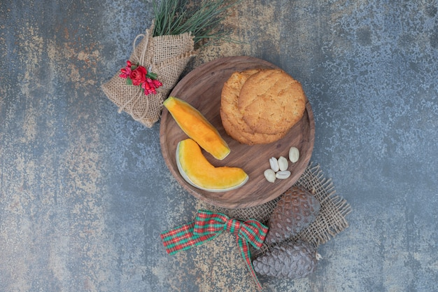 リボンで飾られた木の板にカボチャのクッキーとスライス。高品質の写真 無料写真