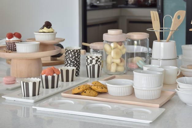 Cookies and cupcakes with cute bakeware setting on white top table Premium Photo