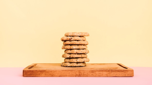 Cookies stack on wooden board on table Free Photo