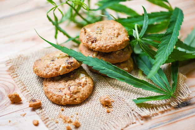 Cookies with cannabis leaf marijuana herb on sack wooden - cannabis food snack for health Premium Photo