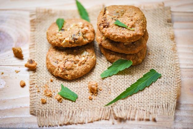 Cookies with cannabis leaf marijuana herb on sack wooden cannabis food snack for health Premium Photo