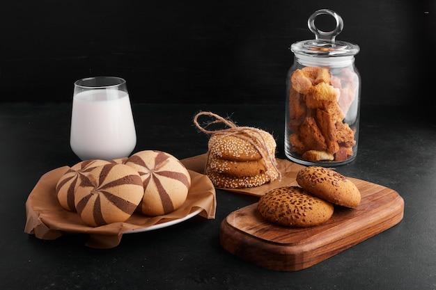 黒の背景に牛乳のガラスとココア、ゴマ、クミンのクッキー。 無料写真