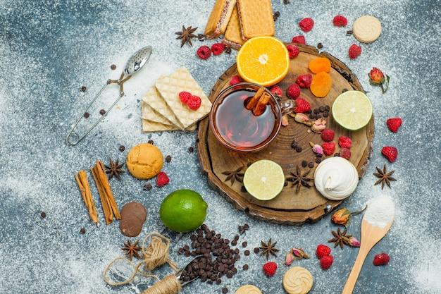 小麦粉、紅茶、果物、スパイス、チョコ、木の板とスタッコの背景、上面にストレーナーとクッキー。 無料写真