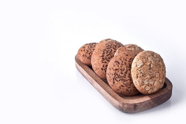 オートミールと白の木製の大皿にクミンのクッキー。 無料写真