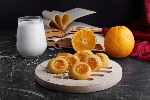 オレンジジャム入りのクッキーに牛乳を添えて。 無料写真