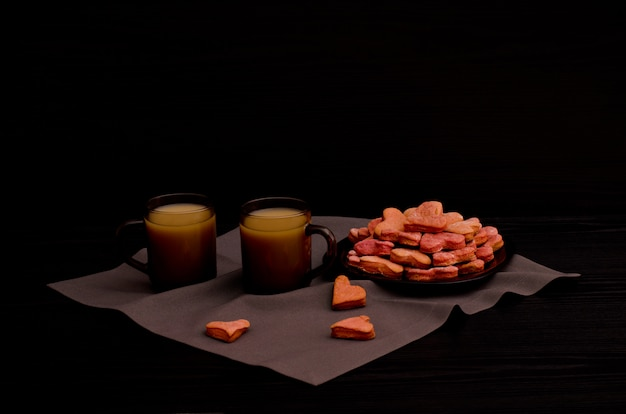Cookies with red heart-shaped, two mugs of coffee, valentine's day Premium Photo