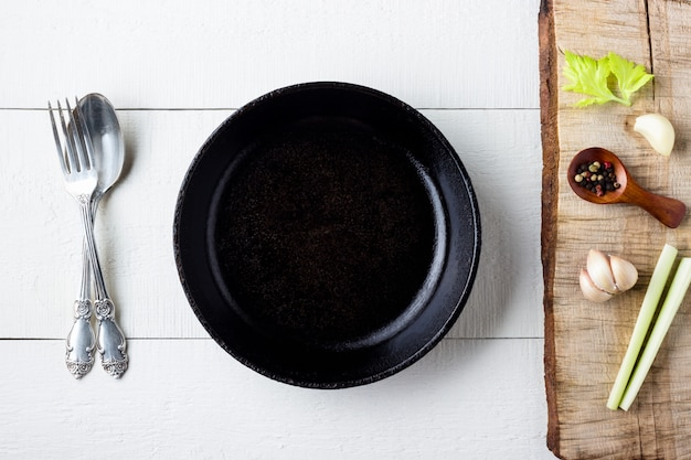 Cooking background concept. empty rustic black cast iron plate, spice and cutlery over wooden background. Premium Photo
