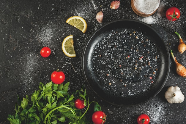 Cooking background ingredients and spices for cooking dinner: tomatoes greens (parsley) salt pepper onions shallots garlic with a frying pan on a black concrete table Premium Photo